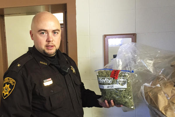 In the evidence room at the courthouse in Deuel County, Neb., Sheriff Adam Hayward holds up a 1-pound bag of marijuana confiscated during a recent traffic stop.