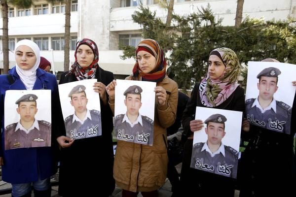 """Anwar al-Tarawneh, center, the wife of Jordanian pilot, Lt. Muath al-Kaseasbeh, who is held by Islamic State group militants, holds a posters of him with Arabic that reads, """"we are all Muath,"""" during a protest in Amman, Jordan, Tuesday, Feb. 3, 2015. Al-Kaseasbeh was seized after his F-16 jet crashed near the Islamic State group's de facto capital, Raqqa, Syria, in December last year.  (Raad Adayleh/AP)"""