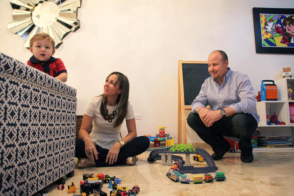 Javier Villa (right) with his wife and son in their home in Puerto Rico.
