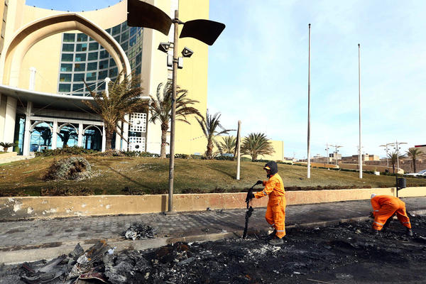 Workers clear the debris from the entrance of Tripoli's Corinthia Hotel, where gunmen blew themselves up after storming the hotel, killing at least nine people on Jan. 28. Multiple factions are fighting for control in Libya, which has two governments.