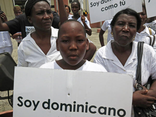 "Demonstrators from a 2013 protest against the Dominican Republic's constitutional amendment restricting citizenship hold signs saying ""I am Dominican just like you."""