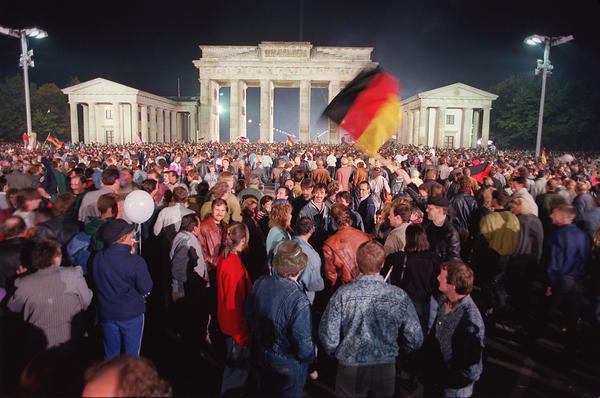 """German youths wave flags as they celebrate the country's reunification at the Brandenburg Gate in Berlin in 1990. One Russian lawmaker recently referred to West Germany's """"annexation"""" of East Germany and said it was less legitimate than Russia's """"reunification"""" with Crimea."""