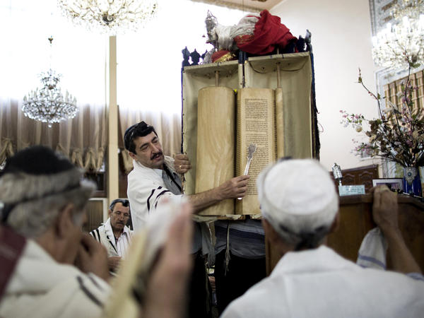 Iranian Jewish men read from the Torah scroll during morning prayers at Youssef Abad Synagogue in Tehran in 2013.