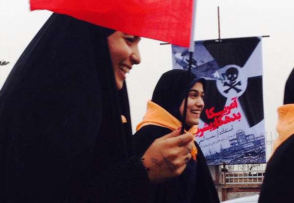 """On the anniversary of Iran's 1979 revolution, young women pass by a banner proclaiming, """"America Owes Humanity."""" (Steve Inskeep and Molly Messick via NPR's On The Road Tumblr)"""