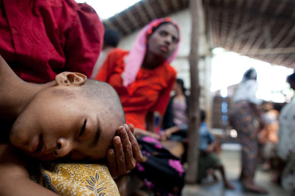 A mother holds her ailing son at a special clinic for malaria in Myanmar.