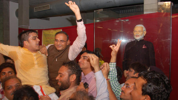 Diamond merchant Lalji Patel, center, celebrates Friday after he made the winning bid of more than 43 million rupees (about $695,000) for Indian Prime Minister Narendra Modi's dark suit with its unique monogram pinstripes.