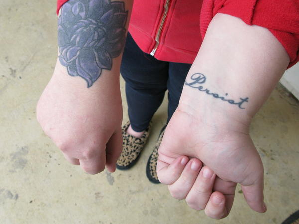 """This woman, who has had her prostitution charge wiped away, says she got the lotus tattoo to cover up the brand of a former pimp. """"Once they put their name on me, I was their property,"""" she adds. She says she got the word """"persist"""" tattooed as a reminder to keep moving forward."""