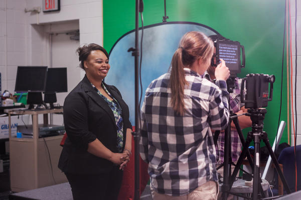 Robyn King watches her students working the teleprompter for the high school morning announcements.