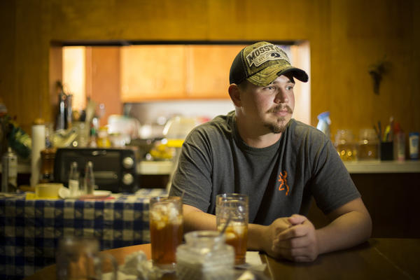 John Coffell sits at his grandmother's table in Hulen, Okla. After he hurt his back at a tire plant last year, his wages dropped so dramatically that he and his family were evicted from their home.