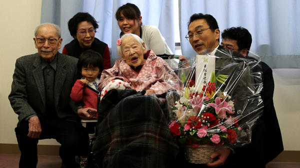 Misao Okawa, the world's oldest living person, poses for a photo with her son Hiroshi Okawa, 92, (left) and other family members and friends on her 117th birthday celebration at Kurenai Nursing Home in Osaka, Japan.