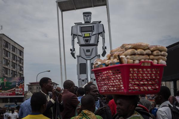 A man walks by with a basket of bread during the official presentation ceremony of three new robots that were installed Tuesday in Kinshasa, Democratic Republic of Congo, to help tackle the city's traffic.