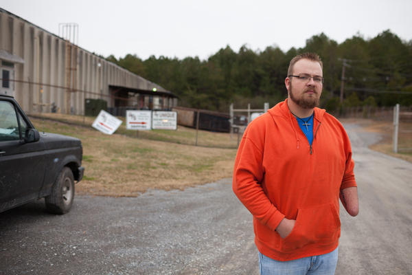 Josh Potter stands in front of the automotive parts plant where he was injured in a work-related incident in September 2013 in LaFayette, Ga.