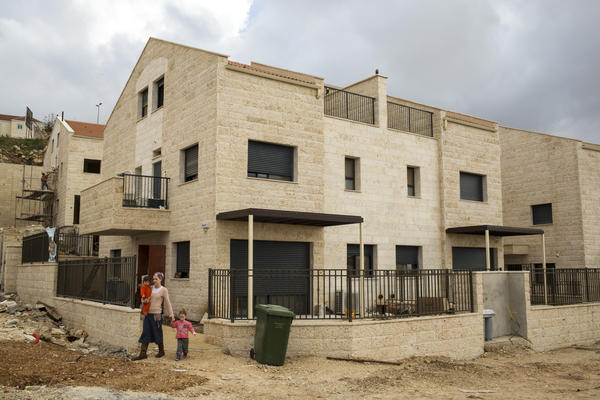 An Israeli settler and her two children leave a friend's house in a new housing development under construction in Ariel, West Bank.