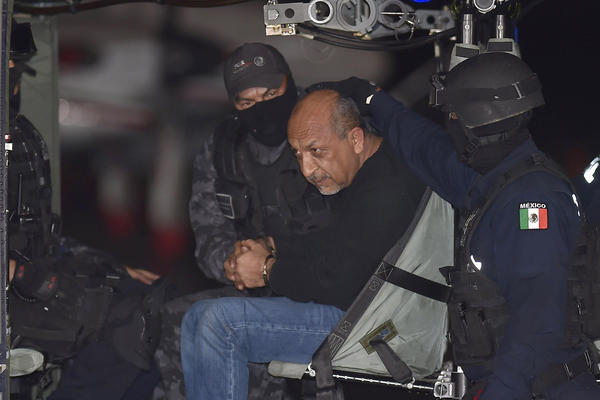 """Mexican federal police escort Servando Gomez (center), aka """"La Tuta,"""" in a helicopter upon his arrival at the airport in Mexico City on Feb. 27. The most-wanted drug lord presided over the Knights Templar cartel in western Michoacan state."""