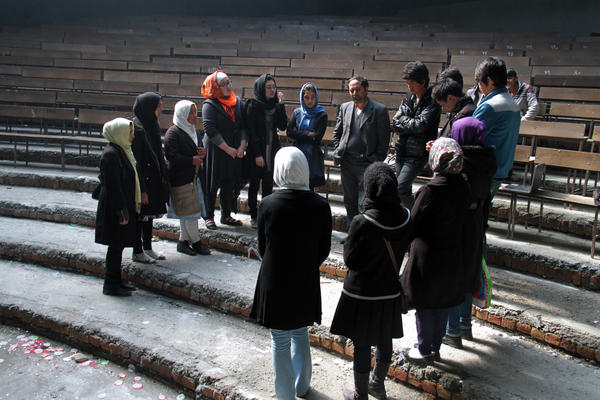 Royesh (center) holds an impromptu class in the auditorium of Marefat School in Kabul.