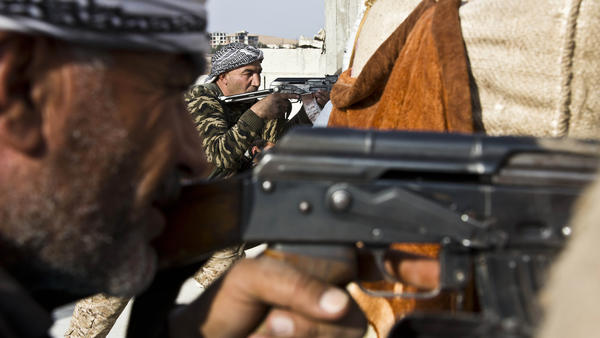 Fighters from the Free Syrian Army and the Kurdish People's Protection Units battle ISIS militants in Kobani, Syria, in November. U.S. officials haven't said whether they will defend the forces if they are attacked by Bashar al-Assad.