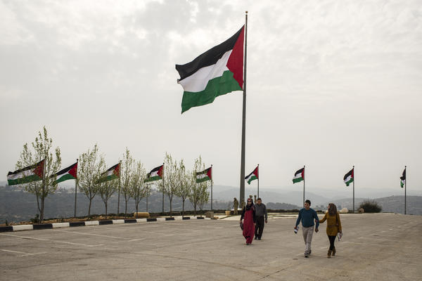 "Palestinians exit the Rawabi showroom after viewing the development. On the ridge behind the Palestinian flag is the Israeli settlement of Ateret. The flag, billed as the biggest Palestinian banner, has been stolen three times, Rawabi employees say --€"" and they blame Israeli settlers."