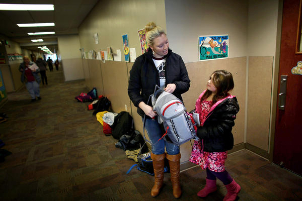 Ashley Bones talks to her stepdaughter, Faith, as she picks her up from elementary school in Watford City, N.D.