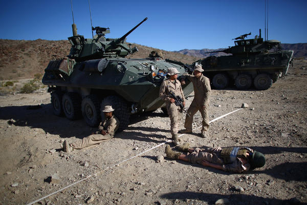 "Marines wait with ""Carl,"" a 220-pound dummy that acts as a stand-in for a wounded Marine during the exercise."