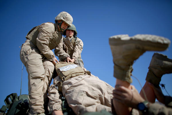 "Marine Lance Cpls. Julia Carroll (left) and Paula Pineda lift ""Carl"" onto the LAV."