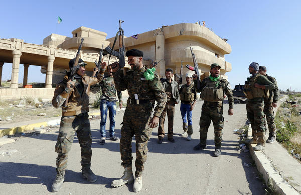"Shiite fighters and Sunni fighters, who have joined Shiite militia groups known collectively as Hashid Shaabi (""Popular Mobilization"") to fight the Islamic State, gesture Tuesday next to former Iraqi President Saddam Hussein's palaces in the Iraqi town of Ouja, near Tikrit."