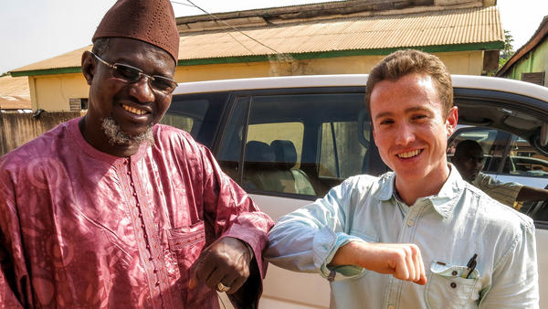 NPR's Kevin Leahy (right) bumps elbows with a Guinean.