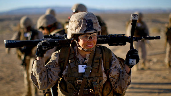 Sgt. Courtney White carries her machine gun before a live fire exercise at the Marine base at Twentynine Palms, Calif.