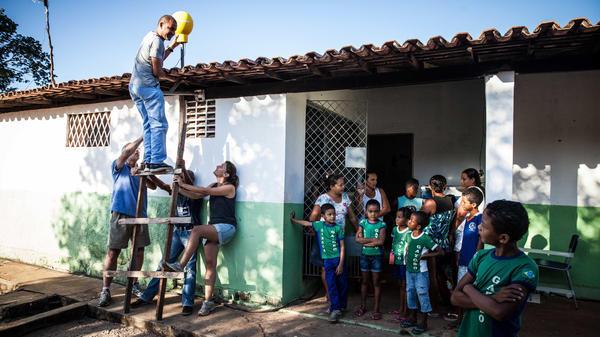 A Google team installed an antenna on a school roof in Agua Fria, Brazil. The antenna will help get an Internet signal.