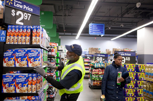 Wal-Mart employee Ernest Reed (left) checks on a cereal display at the Washington, D.C., location where he works. He was one of about 23,000 people who applied for hundreds of job openings when Wal-Mart first arrived in D.C.