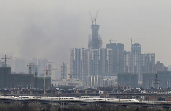 A bullet train runs past buildings under construction in Wuhan, in central China's Hubei province, Feb. 28. Factories are moving inland because of economic pressures — and migrant workers are following them.