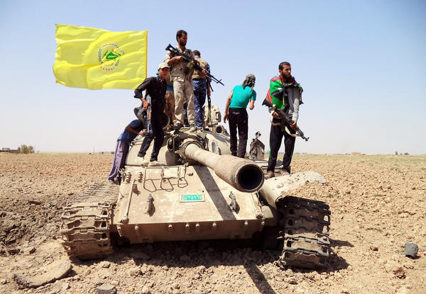 Members of a Shiite militia, Kataib Hezbollah, stand on a tank during fighting against Islamic State extremists near Tikrit last year.