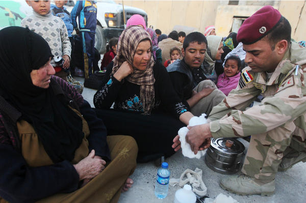 A displaced Iraqi Sunni woman receives medical treatment from a soldier after arriving at an army camp in the city of Samarra on March 8. She was among the many who fled villages like al-Dour because of fighting between ISIS militants on one side and government and Shiite militia forces on the other.