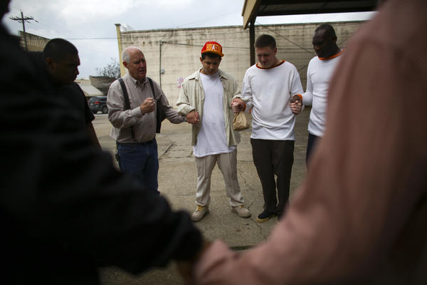 Bill Kleiber, director of Restorative Justice Ministries, in suspenders, leads a circle of released inmates in a prayer shortly before they board a bus.