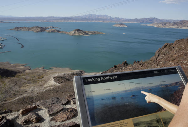 Dropping water levels reveal larger islands in Lake Mead compared with a picture on an interpretive sign overlooking the lake in the Lake Mead National Recreation Area in Nevada. A 14-year drought has caused the water level in the reservoir to shrink to its lowest point since it was first filled in the 1930s.