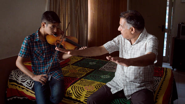 Saleem Khan, 65, teaches his grandson how to play the violin in their home in Lahore.
