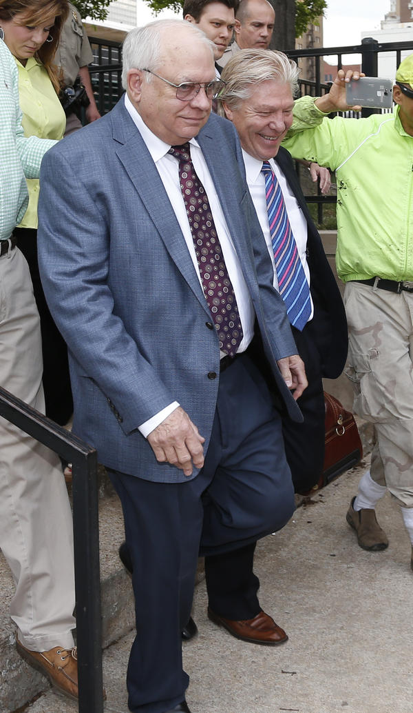Robert Bates (left), a Tulsa County, Okla., reserve deputy, leaves his arraignment Tuesday with his attorney. Bates fatally shot a suspect who was pinned down by officers, raising alarms about volunteer police officers who wear badges and carry guns.