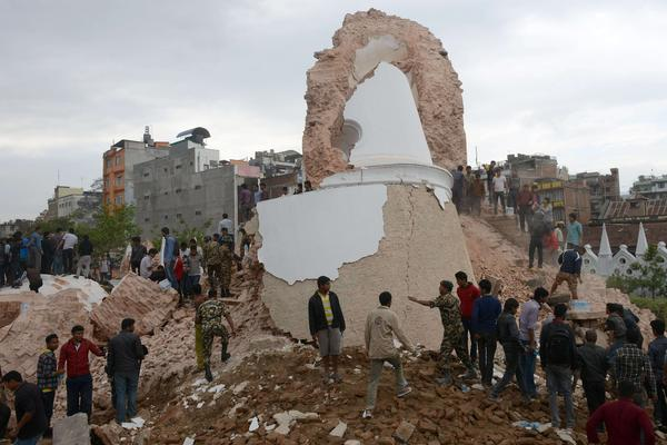 Nepalese rescue members and onlookers gather at the collapsed Dharahara Tower in Kathmandu.