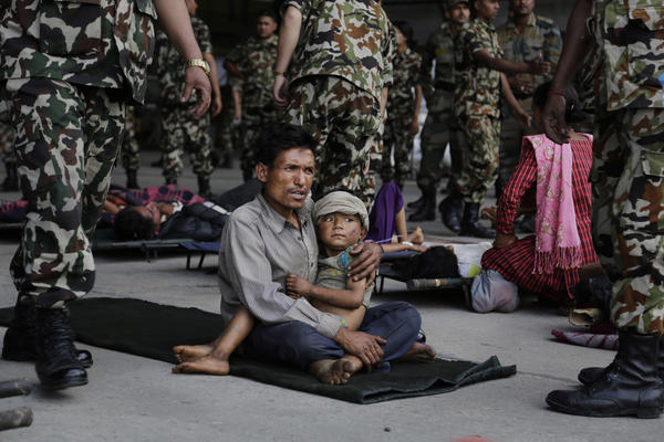 A man and child wait for ambulances after being evacuated at the airport in Kathmandu, Nepal, on Monday. The devastating earthquake that hit Nepal on Saturday is now blamed for at least 4,000 deaths. <br /><br />