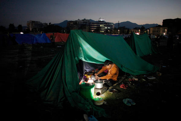 A Nepalese man cooks food inside a tent as people relocate to open ground from fears of earthquake tremors in Kathmandu, Nepal, on Monday evening.