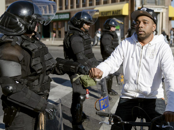 A man on a bicycle greets Maryland state troopers on Tuesday in the aftermath of rioting in Baltimore.