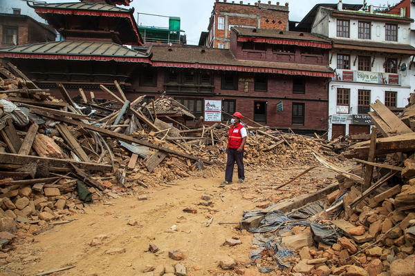 An earthquake emergency team member walks through debris from one of the UNESCO World Heritage site temples in Basantapur Durbar Square in Kathmandu.