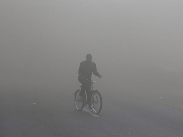 A man rides a bicycle through heavy smoke from a fire at a nearby store on Monday during unrest following the funeral of Freddie Gray in Baltimore.