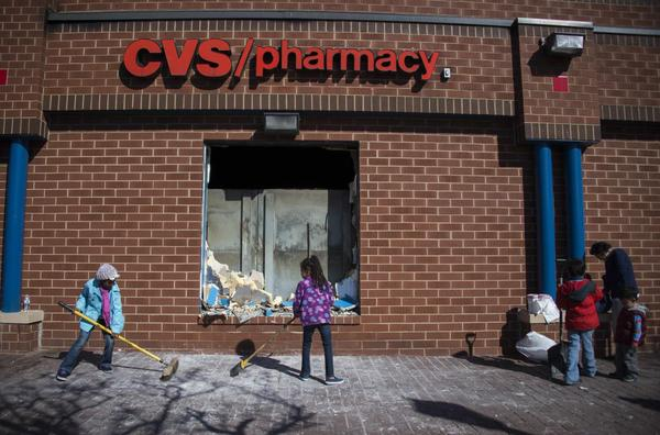 Young children sweep up the area outside the CVS Pharmacy in Baltimore, Maryland, April 28, 2015, that was set on fire during rioting last night. Riot police and National Guard troops stood guard on the smoldering streets of Baltimore Tuesday after protesters incensed by the death of a young black man in police custody went on the rampage, torching cars and buildings and looting stores. Fires continued to burn in the mainly black northeastern city, where a curfew was set to take effect Tuesday evening after a day of riots that dragged on into Monday night. The state of Maryland declared a state of emergency after rioters ransacked shops, making off with armloads of merchandise. Schools were closed Tuesday a safety measure. (Jim Watson/AFP/Getty Images)