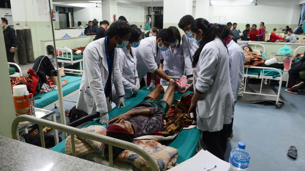 People injured in a devastating earthquake receive treatment at a hospital in Kathmandu, Nepal's capital, on Tuesday. Hungry and desperate villagers rushed toward relief helicopters in remote areas of Nepal, begging to be airlifted to safety.