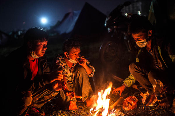 Earthquake survivors warm themselves around a bonfire at a makeshift camp at Tunshikel park in Kathmandu, Nepal, on Tuesday. More than 5,000 people are confirmed dead from Saturday's earthquake.