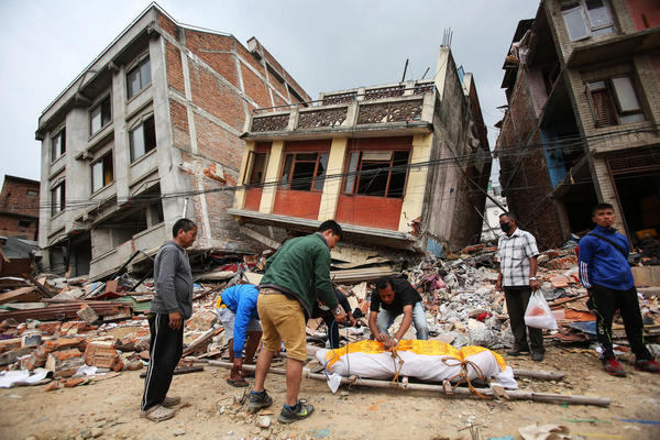 Nepalese men carry a dead body in the badly damaged capital, Kathmandu. The BBC reports that 1.4 million of the 8 million people affected need food aid, citing the United Nations saying that there also are severe shortages of body bags and medical supplies.
