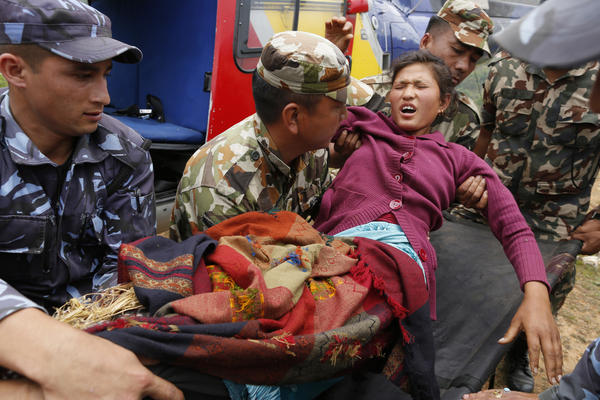 Sita Karka, who broke both of her legs during the earthquake, arrives by helicopter in Gorkha to be treated for her injuries. Helicopters crisscrossed the skies above the high mountains of Gorkha district near the epicenter of the weekend earthquake, ferrying the injured to clinics and taking emergency supplies back to remote villages devastated by the disaster.