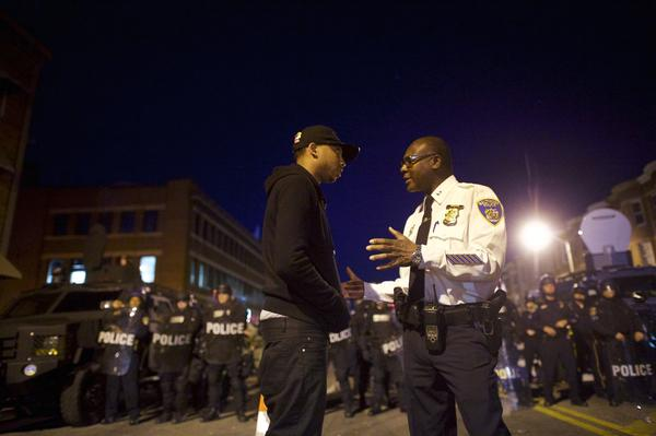 A Baltimore police captain talks to a protester. The Maryland National Guard troops are positioned across parts of the city a day after riots that left at least 20 officers injured and more than a dozen buildings damaged, destroyed or looted.