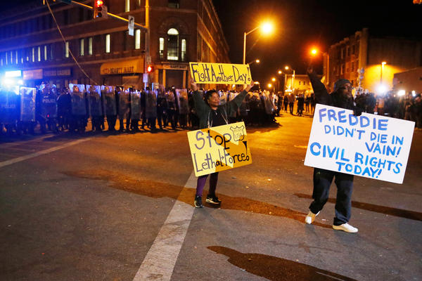Protesters hold up signs in front of a line of police.