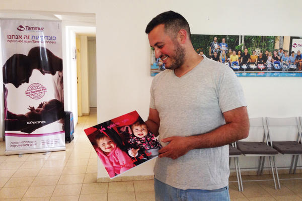 Roy Youldous is a manager at Tammouz, the Israeli agency that set up the surrogate mother for the Greengolds. He's holding a photo of his twin daughters, who were carried by a surrogate.